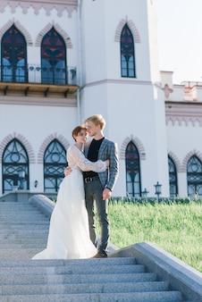 Jovem noiva e noivo casal concurso, abraçando-se. casamento de verão, ruiva feminina e masculina.