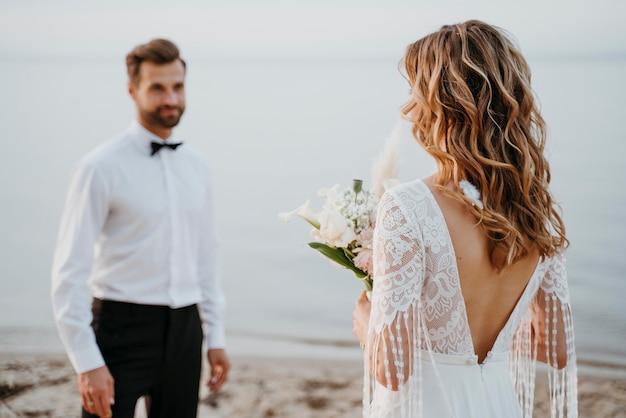 Jovem noiva e noivo fazendo um casamento na praia