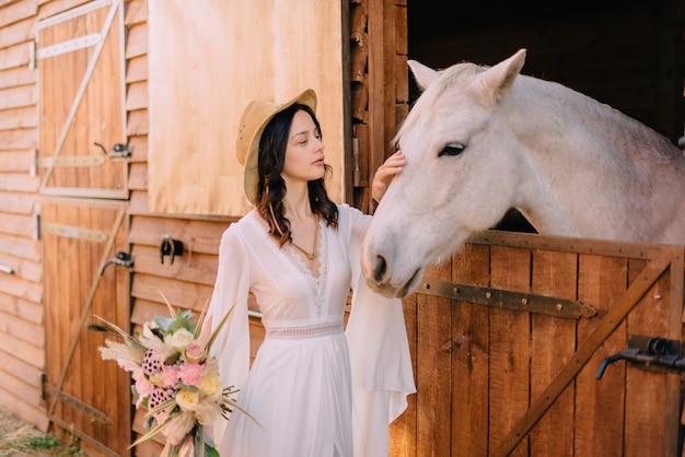 Jovem noiva em estilo boho acariciando o cavalo branco