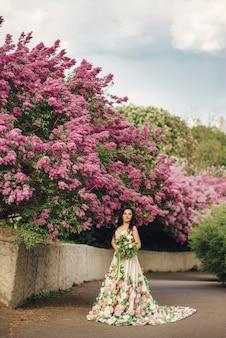 Jovem noiva em um luxuoso vestido de flores em um jardim lilás florido