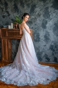 Jovem noiva em vestido longo posando para a câmera