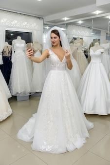 Jovem noiva fazendo selfie com vestido de noiva em salão