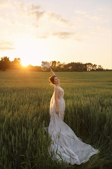 Jovem noiva feliz em um vestido de noiva de renda, segurando um buquê de flores na mão e posando no campo ao pôr do sol de verão.