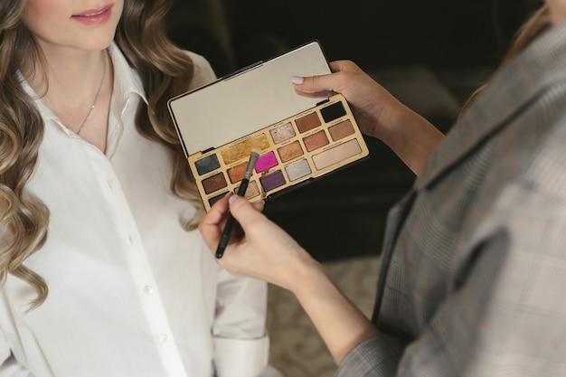 Jovem noiva linda aplicar maquiagem de casamento de um maquiador. treinamento matinal.