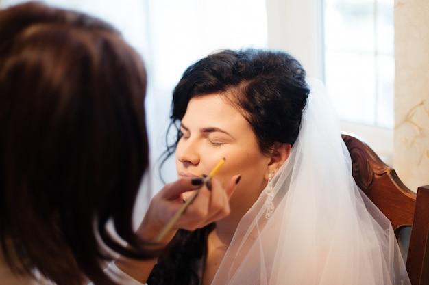 Jovem noiva linda aplicar maquiagem de casamento pelo maquiador