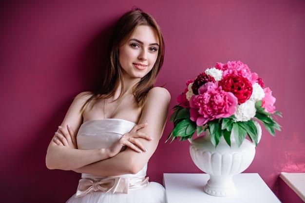 Jovem noiva linda com um buquê de peônia rosa perto da parede