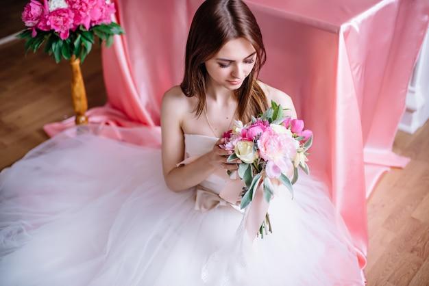 Jovem noiva linda com um buquê de peônia rosa