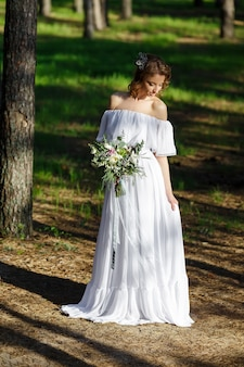 Jovem noiva linda em pé na floresta