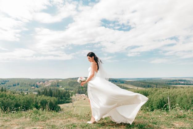 Jovem noiva linda no vestido de casamento branco posando em uma colina na natureza