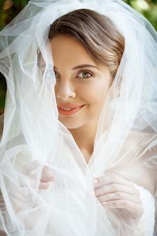 Jovem noiva loira linda no vestido de casamento e véu sorrindo.