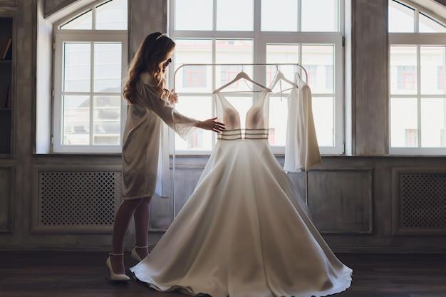 Jovem noiva morena bonita olhando para o vestido de casamento.