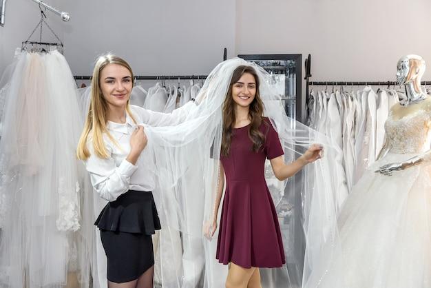 Jovem noiva posando com véu em salão de casamento