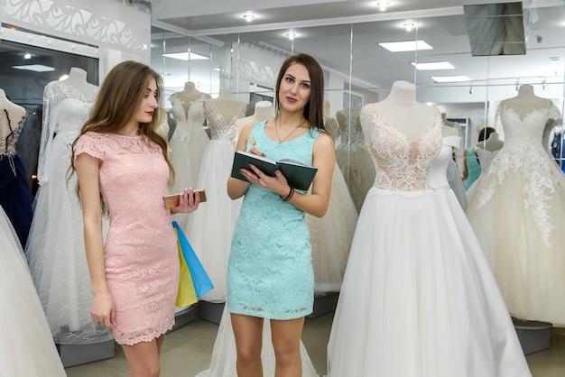 Jovem noiva reservando vestido de noiva em revendedor em salão