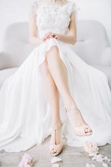 Jovem noiva sentada no sofá com as pernas nuas em sapatos de salto alto rosa e pétalas de flores cor de rosa. conceito de moda de casamento festivo.