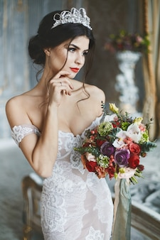 Jovem noiva vestido de renda posando com bouquet de noiva