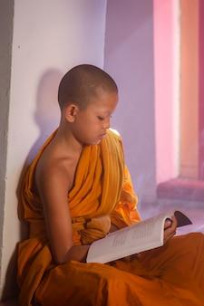 Jovem noviço monge lendo um livro no parque histórico de ayutthaya na tailândia