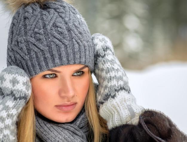 Jovem num casaco de pele quente, chapéu, luvas e cachecol.