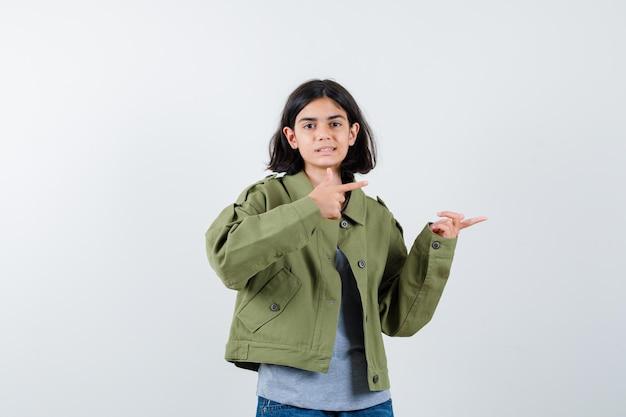Jovem num suéter cinza, jaqueta cáqui, calça jeans apontando para a direita com o dedo indicador e parecendo feliz, vista frontal.