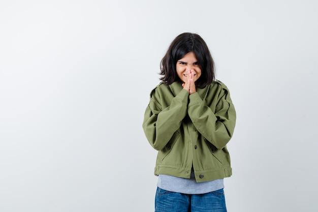 Jovem num suéter cinza, jaqueta cáqui, calça jeans, mostrando o gesto namastê e olhando fofa, vista frontal.