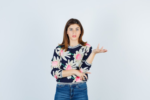 Jovem num suéter floral, jeans, esticando a mão de forma questionadora e parecendo perplexa, vista frontal.