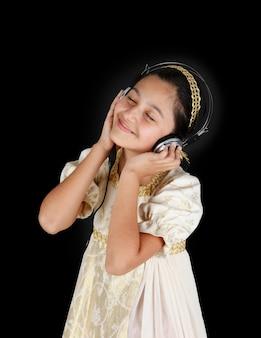 Jovem num vestido antigo enquanto ouve música com fones de ouvido na parede preta.