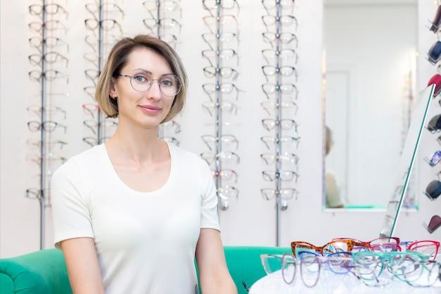 Jovem numa loja de ótica escolhendo novos óculos com oculista