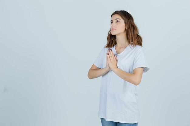 Jovem numa t-shirt branca, mostrando o gesto namastê e olhando esperançosa, vista frontal