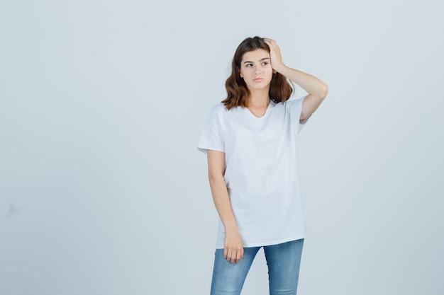 Jovem numa t-shirt branca, segurando a mão na cabeça e olhando pensativa, vista frontal.