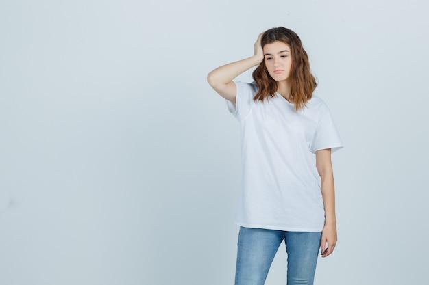 Jovem numa t-shirt branca, segurando a mão na cabeça e parecendo chateada, vista frontal.
