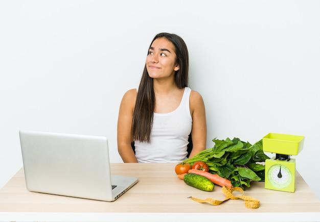 Jovem nutricionista asiática isolada na parede branca, sonhando em alcançar objetivos e propósitos
