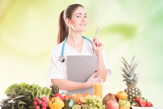 Jovem nutricionista sentada à mesa e mostrando frutas e vegetais coloridos
