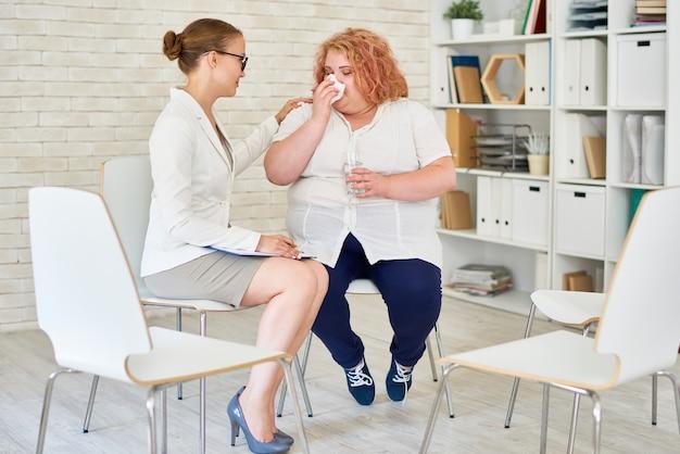 Jovem obesa chorando em reunião com psiquiatra