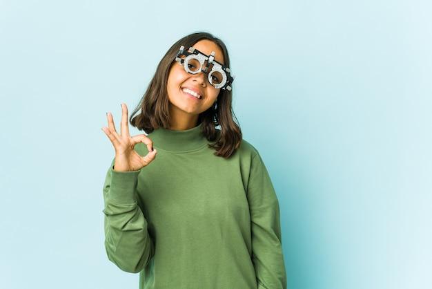 Jovem oculista latina sobre parede isolada pisca um olho e segura um gesto de ok com a mão.