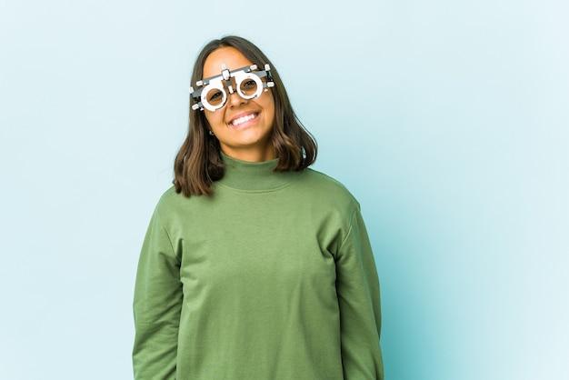 Jovem oculista mulher latina sobre a parede isolada encolhe os ombros e abre os olhos confusos.