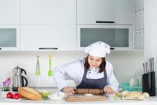 Jovem ocupada comis chef de uniforme em pé atrás da mesa preparando massa na cozinha branca