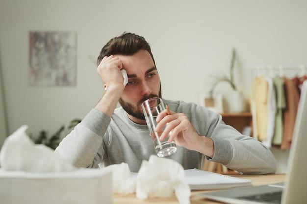 Jovem ocupado com um lenço na mão tomando um copo d'água enquanto ficava em casa durante uma doença e trabalhando remotamente