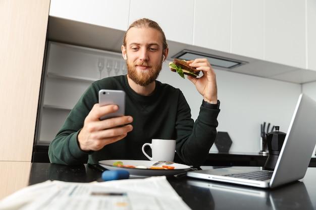 Jovem ocupado trabalhando em um laptop em casa, sentado na cozinha, bebendo chá, almoçando