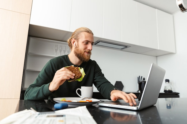 Jovem ocupado trabalhando em um laptop em casa, sentado na cozinha, bebendo chá