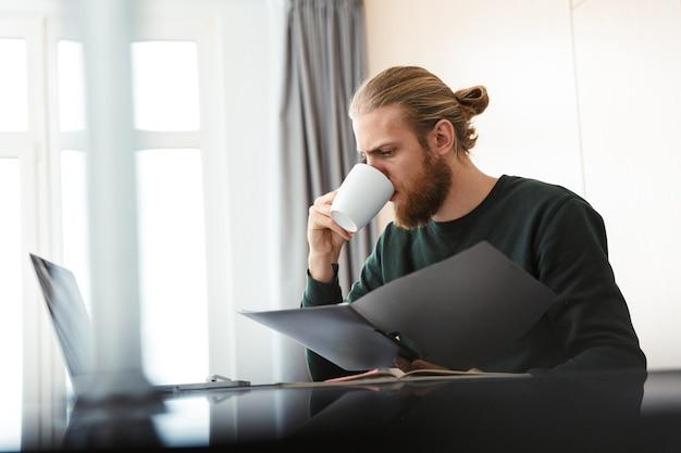 Jovem ocupado trabalhando em um laptop em casa, sentado na cozinha