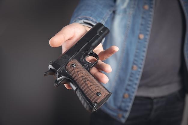 Jovem oferece uma pistola preta.