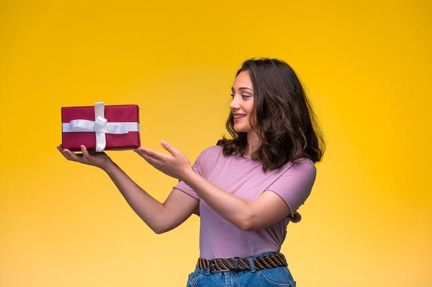 Jovem oferecendo uma caixa de presente vermelha e sorrindo, vista de perfil.