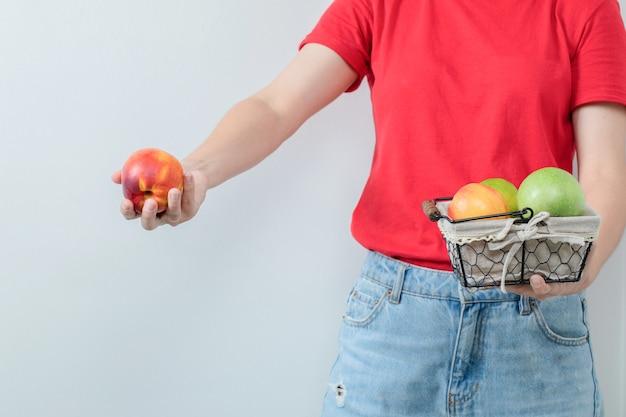 Jovem, oferecendo uma cesta de frutas na mão.