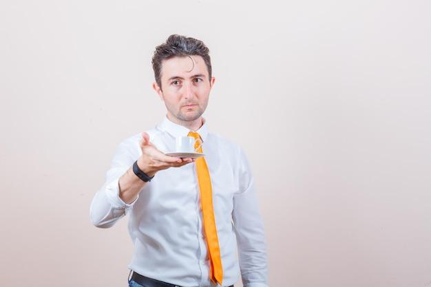 Jovem oferecendo uma xícara de café turco de camisa branca, gravata e parecendo gentil