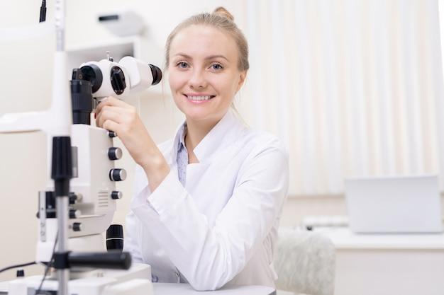 Jovem oftalmologista contemporâneo feliz com equipamento de check-up da visão olhando para você nas clínicas