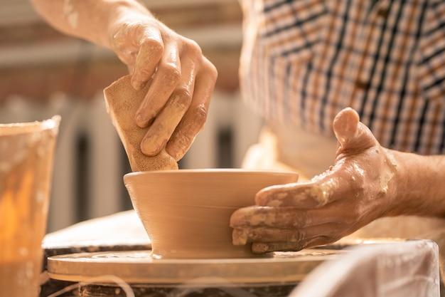 Jovem oleiro com uma esponja segurando-o perto de um pote de barro giratório enquanto dá forma ao pote durante o trabalho