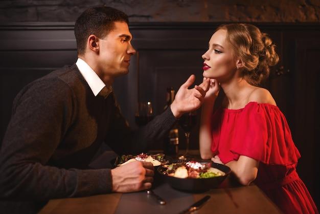 Jovem olha para os olhos de uma mulher atraente e elegante em um vestido vermelho no restaurante. relacionamento de lindo casal apaixonado, noite romântica