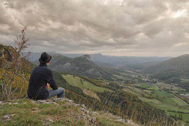 Jovem, olhando a montanha ao pôr do sol