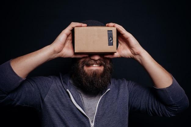 Jovem olhando através de um fone de ouvido de papelão de realidade virtual