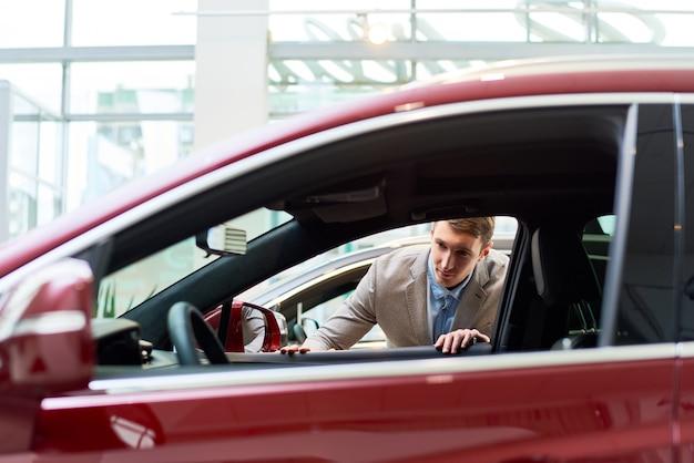 Jovem olhando carros no showroom