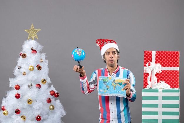 Jovem olhando de frente segurando o mapa-múndi e o globo ao redor da árvore de natal e presentes